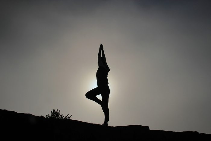 Person striking a yoga pose. Yoga can be tracked using an Apple Watch